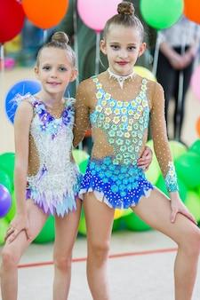 Pequenas ginastas com medalhas na competição de ginástica rítmica