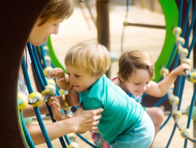 Pequenas irmãs com mãe no parque infantil