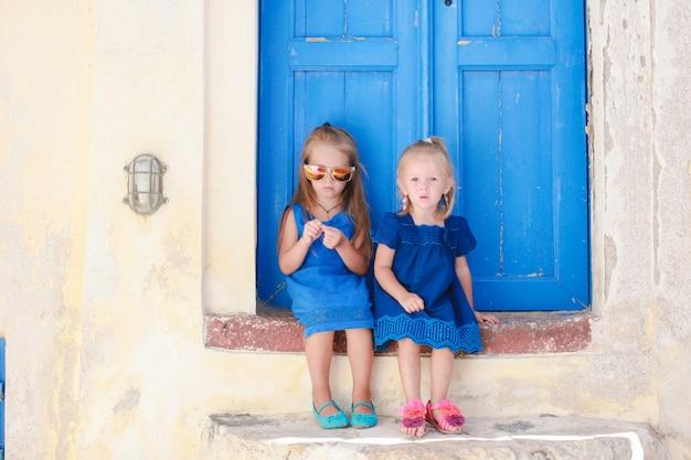 Pequenas irmãs fofos sentado perto da antiga porta azul na aldeia grega de emporio, santorini