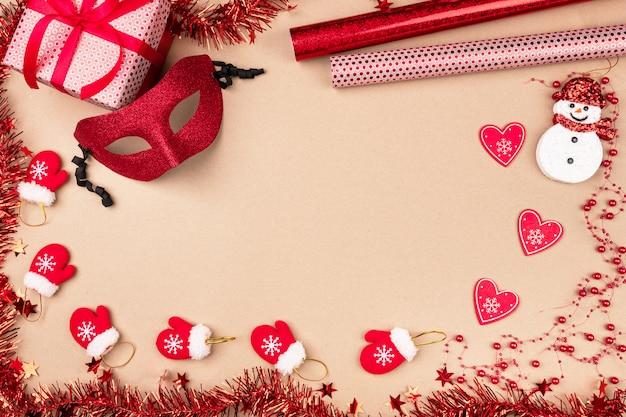Pequenas luvas vermelhas estão espalhadas sobre um fundo bege com um presente permanente em embalagem prateada com um boneco de neve fofo, corações de papel, miçangas e uma máscara de baile de máscaras cercada por enfeites de natal. festivo.