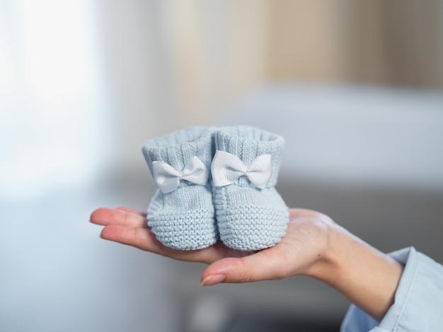 Pequenas meias de malha azuis com um laço na mão da mulher