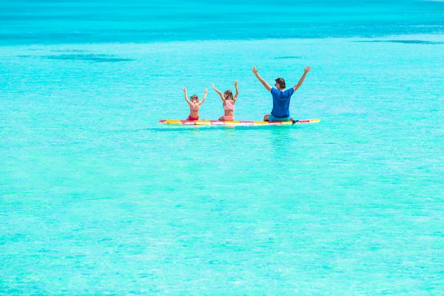 Pequenas meninas e jovem pai na prancha de surf durante as férias de verão