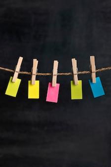 Pequenas notas brilhantes penduradas com prendedores de roupa na corda. fundo preto. lugar para o seu texto. lembrete. quadro vertical.