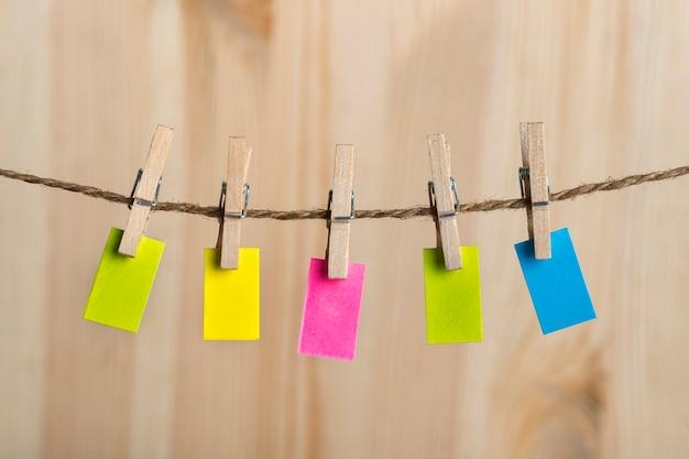 Pequenas notas multicoloridas penduradas com prendedores de roupa na corda. copie o espaço. lugar para o seu texto. nota, lembrete.