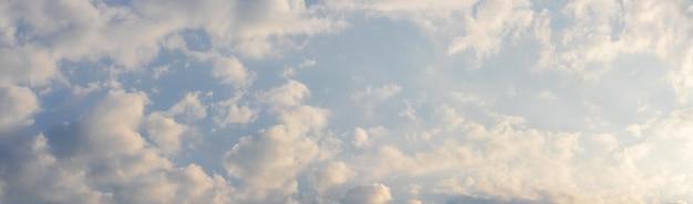 Pequenas nuvens brancas e rosa no céu da manhã sob luz solar intensa