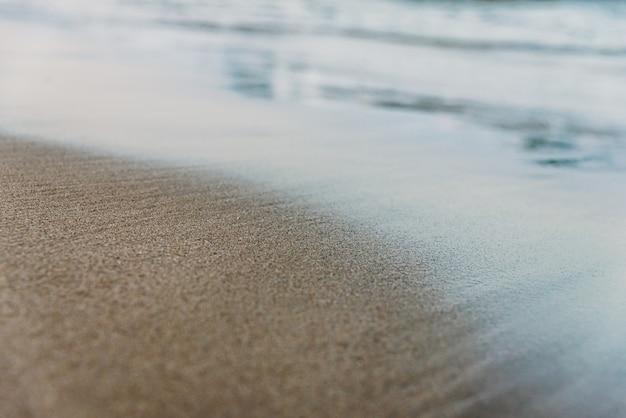 Pequenas ondas atingem a costa de uma praia serena e molham a areia fina