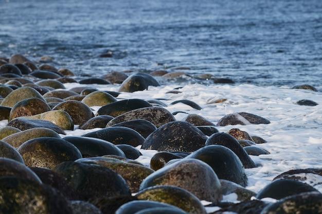 Pequenas ondas do mar quebram contra as pedras da costa.