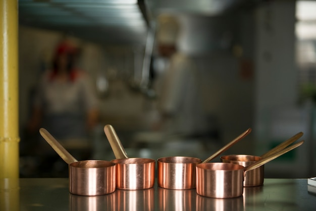 Pequenas panelas de cobre em uma mesa de cozinha do restaurante
