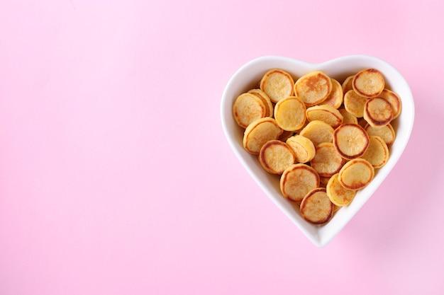 Pequenas panquecas no café da manhã em um coração em forma de tigela branca em uma superfície rosa, comida da moda, copie o espaço para texto ou desenho