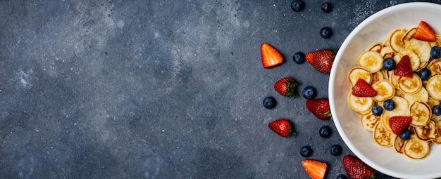 Pequenas panquecas no café da manhã. panquecas com morangos e mirtilos cozidos de manhã no café da manhã na cozinha de casa. bandeira de comida fundo.