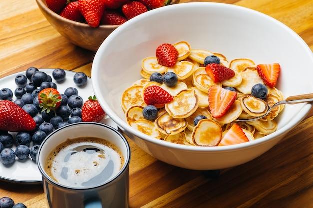 Pequenas panquecas no café da manhã. panquecas com morangos e mirtilos cozidos de manhã no café da manhã na cozinha de casa.