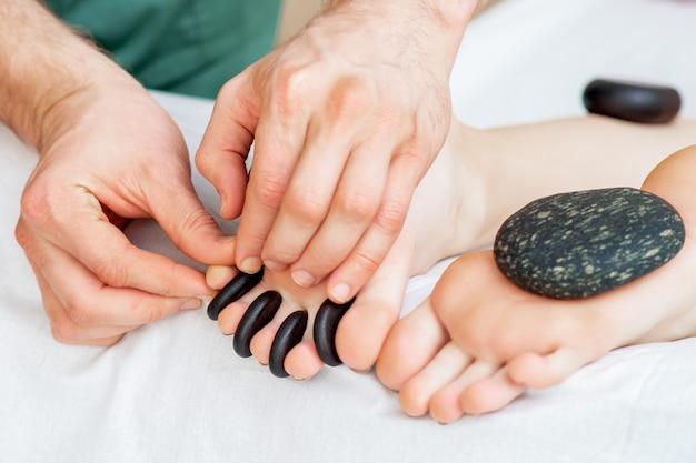 Pequenas pedras negras quentes entre dedos femininos