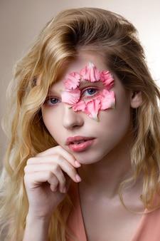 Pequenas pétalas. mulher terna de olhos azuis com cabelo loiro ondulado e pequenas pétalas de rosa ao redor do olho