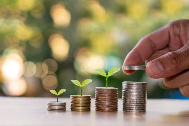Pequenas pilhas de moedas com pequenas plantas e uma mão pegando uma moeda.