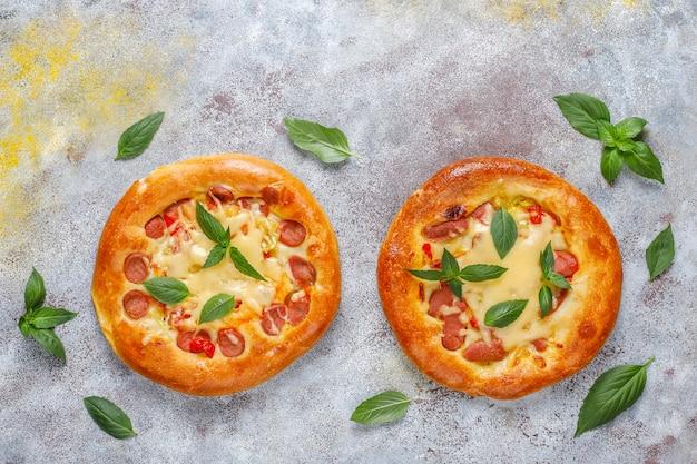 Pequenas pizzas caseiras frescas com manjericão.