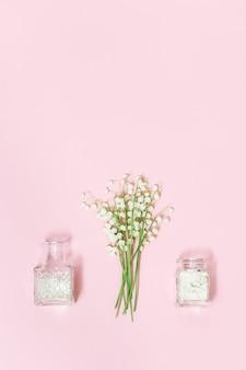 Pequenas primeiras flores da primavera, lírios do vale e um lindo frasco de vidro com