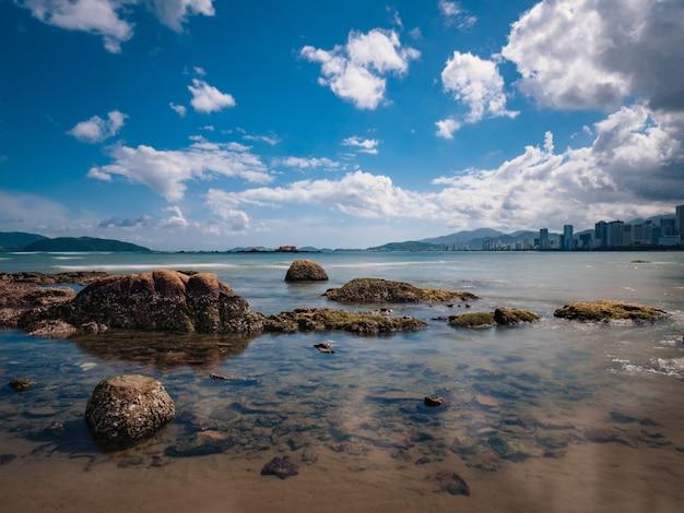 Pequenas rochas no mar com fundo de ilhas. céu azul nublado