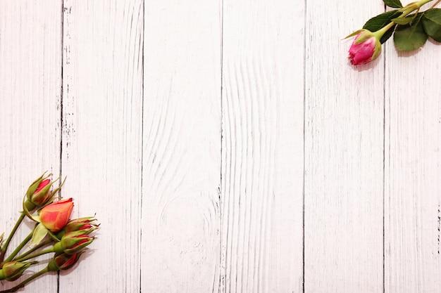 Pequenas rosas em fundo branco de madeira