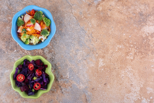 Pequenas tigelas com diferentes saladas expostas na superfície de mármore