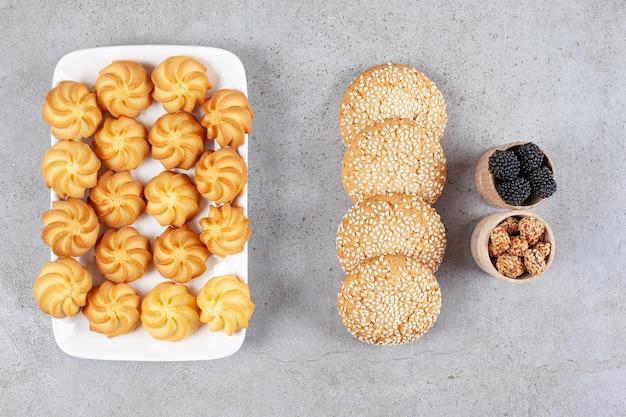 Pequenas tigelas de amoras e amendoim glaceado ao lado de biscoitos em um prato e na superfície de mármore.