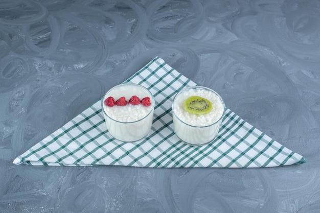 Pequenas tigelas de arroz com leite guarnecido com framboesas e uma fatia de kiwi em uma toalha de mesa na mesa de mármore.