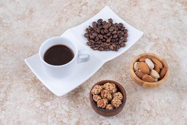 Pequenas tigelas de lanche ao lado de uma pilha de grãos de café e uma xícara de café