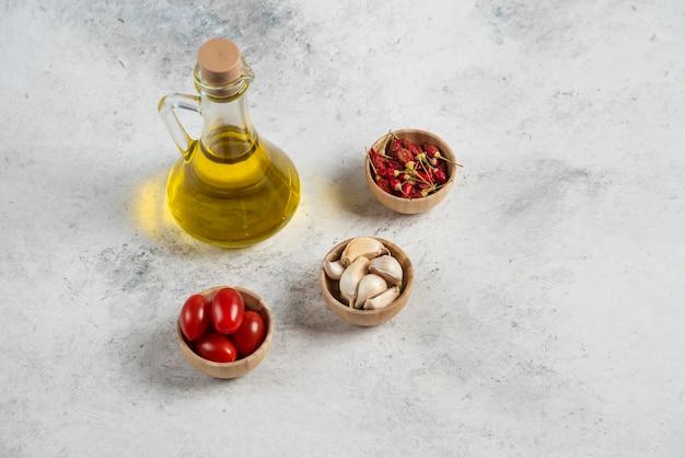 Pequenas tigelas de madeira com legumes e azeite em fundo de mármore.