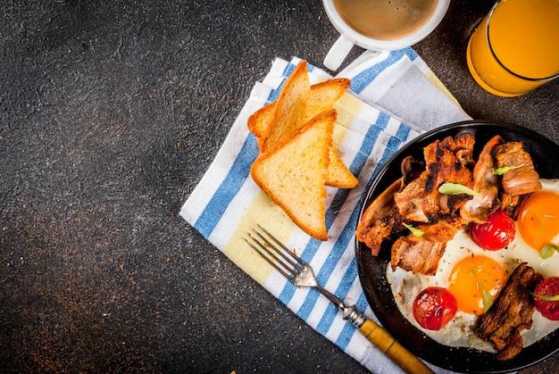 Pequeno-almoço americano inglês caseiro tradicional, ovos fritos, torradas, bacon, com caneca de café