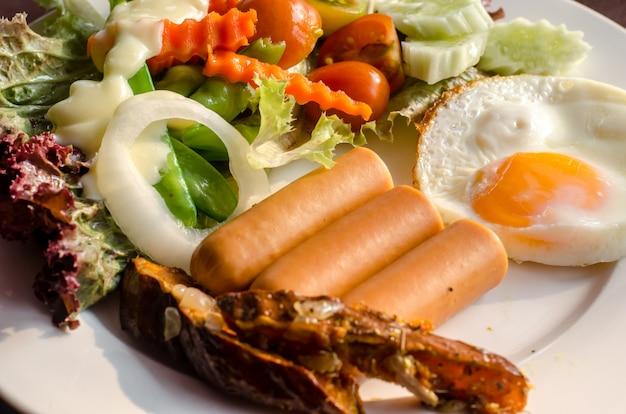 Pequeno-almoço americano, ovo frito, salsicha, misture frutas e vegetais no prato