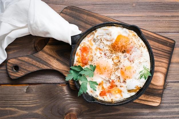 Pequeno-almoço caseiro de shakshuka ovos fritos com tomate e ervas em uma panela sobre uma mesa de madeira