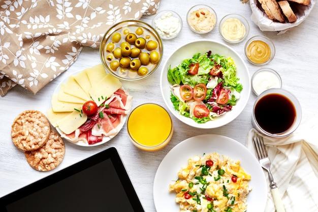 Pequeno-almoço continental fresco. comida saudável. tablet, tela preta.