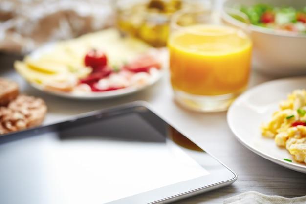 Pequeno-almoço continental fresco. tablet, tela preta, foco seletivo.
