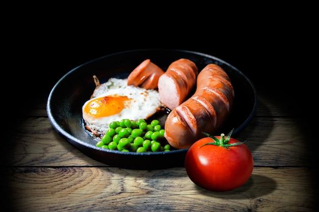 Pequeno-almoço de ovos fritos, salsichas, ervilhas e tomate em uma mesa velha de madeira