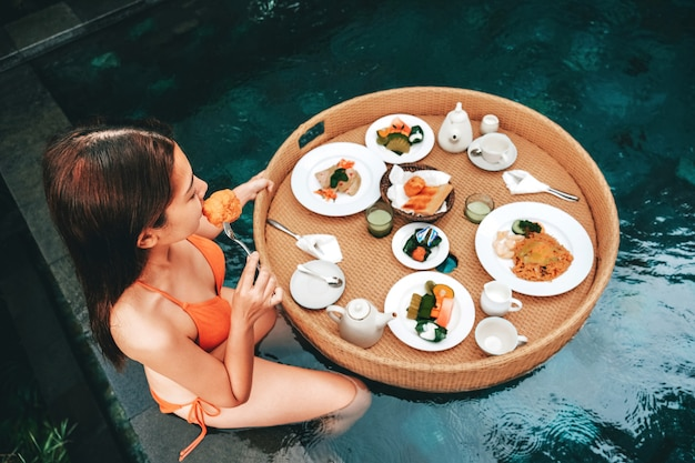Pequeno-almoço flutuante na piscina infinita na piscina do paraíso, manhã no resort tropical bali, indonésia