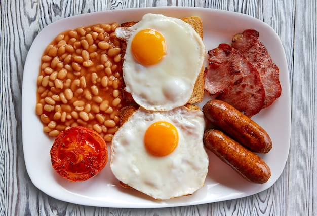 Pequeno-almoço inglês com dois ovos, feijão de salsicha