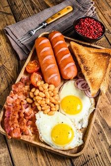 Pequeno-almoço inglês em tabuleiro de madeira com ovos estrelados, salsichas, bacon, feijão e tostas.