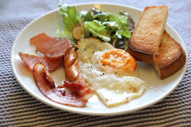 Pequeno-almoço inglês ovo frito bacon salsicha pão e salada