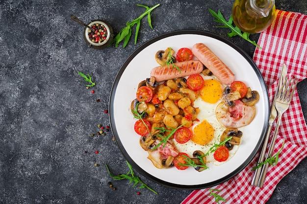 Pequeno-almoço inglês - ovo frito, feijão, tomate, cogumelos, bacon e salsicha. comida saborosa.