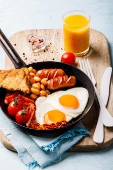 Pequeno-almoço inglês tradicional. forma de coração de ovos