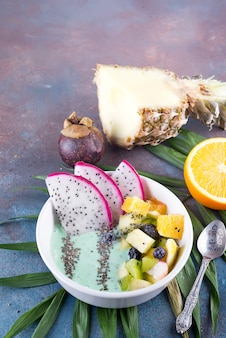 Pequeno-almoço kiwi batido tigela coberta com pitaya, abacaxi, sementes de chia e bagas com folha de palmeira sobre fundo de pedra, vista superior