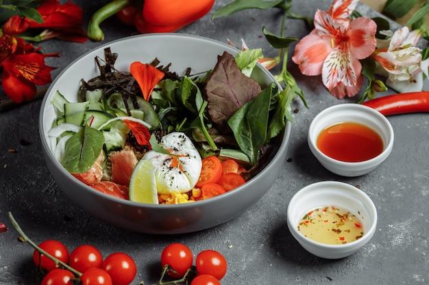 Pequeno-almoço leve saudável fresco, almoço de negócios. café da manhã com ovo pochê, trigo sarraceno, peixe vermelho