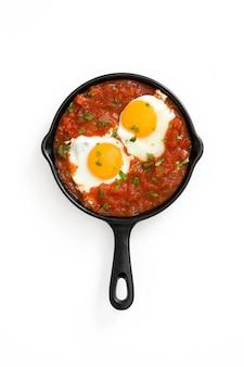 Pequeno-almoço mexicano huevos rancheros na frigideira de ferro branco