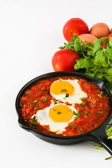 Pequeno-almoço mexicano huevos rancheros na frigideira de ferro isolada no branco