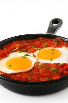 Pequeno-almoço mexicano huevos rancheros na frigideira de ferro isolada no fundo branco