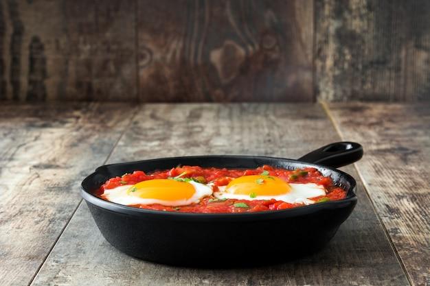 Pequeno-almoço mexicano huevos rancheros na frigideira de ferro na mesa de madeira