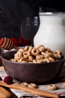 Pequeno-almoço saudável - anéis de cereais em uma tigela com leite
