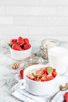 Pequeno-almoço saudável, aveia durante a noite com leite e morango fresco
