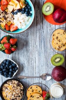 Pequeno-almoço saudável, cereais com iogurte, morangos, mirtilo, maçã, banana, em madeira rústica. vista do topo