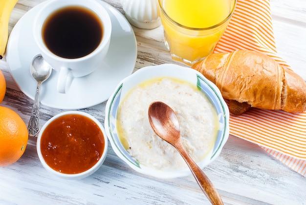 Pequeno-almoço saudável com aveia com manteiga, croissant e café