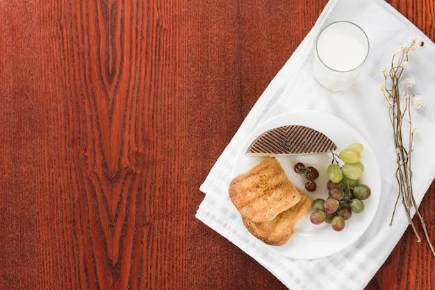 Pequeno-almoço saudável com copo de leite na toalha de mesa branca sobre o fundo de madeira